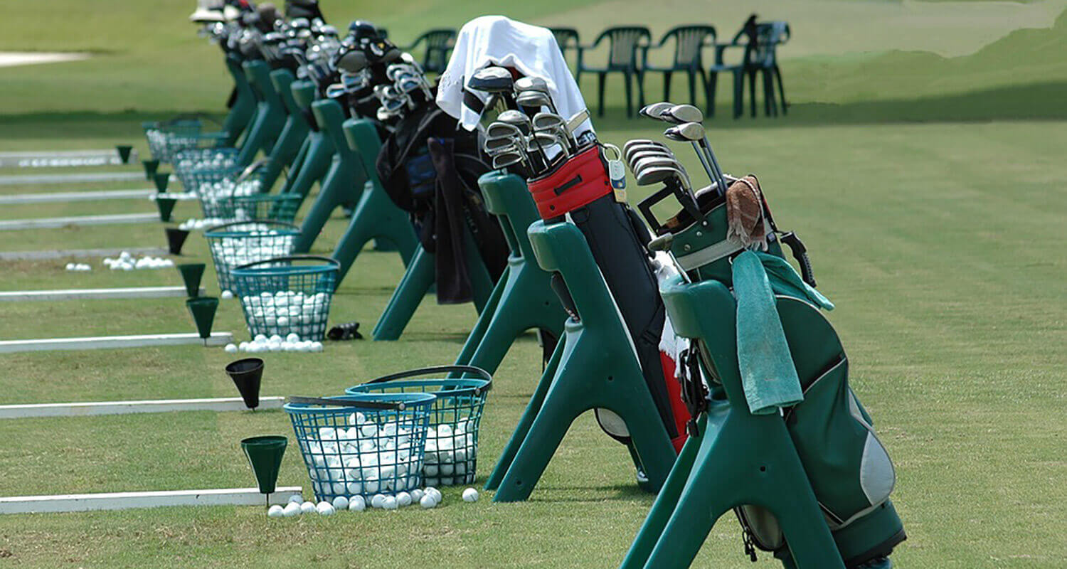 Golf bags lined up with golf balls